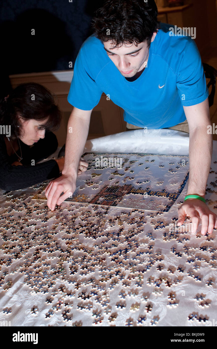 two people work on jigsaw puzzle - Stock Image