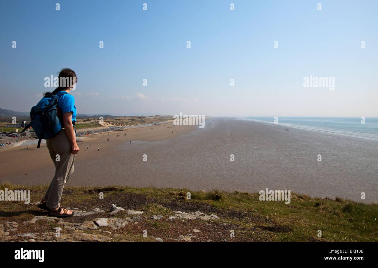 Hiker on headland on Carmarthen Bay Coast Path Pendine sands Wales UK - Stock Image