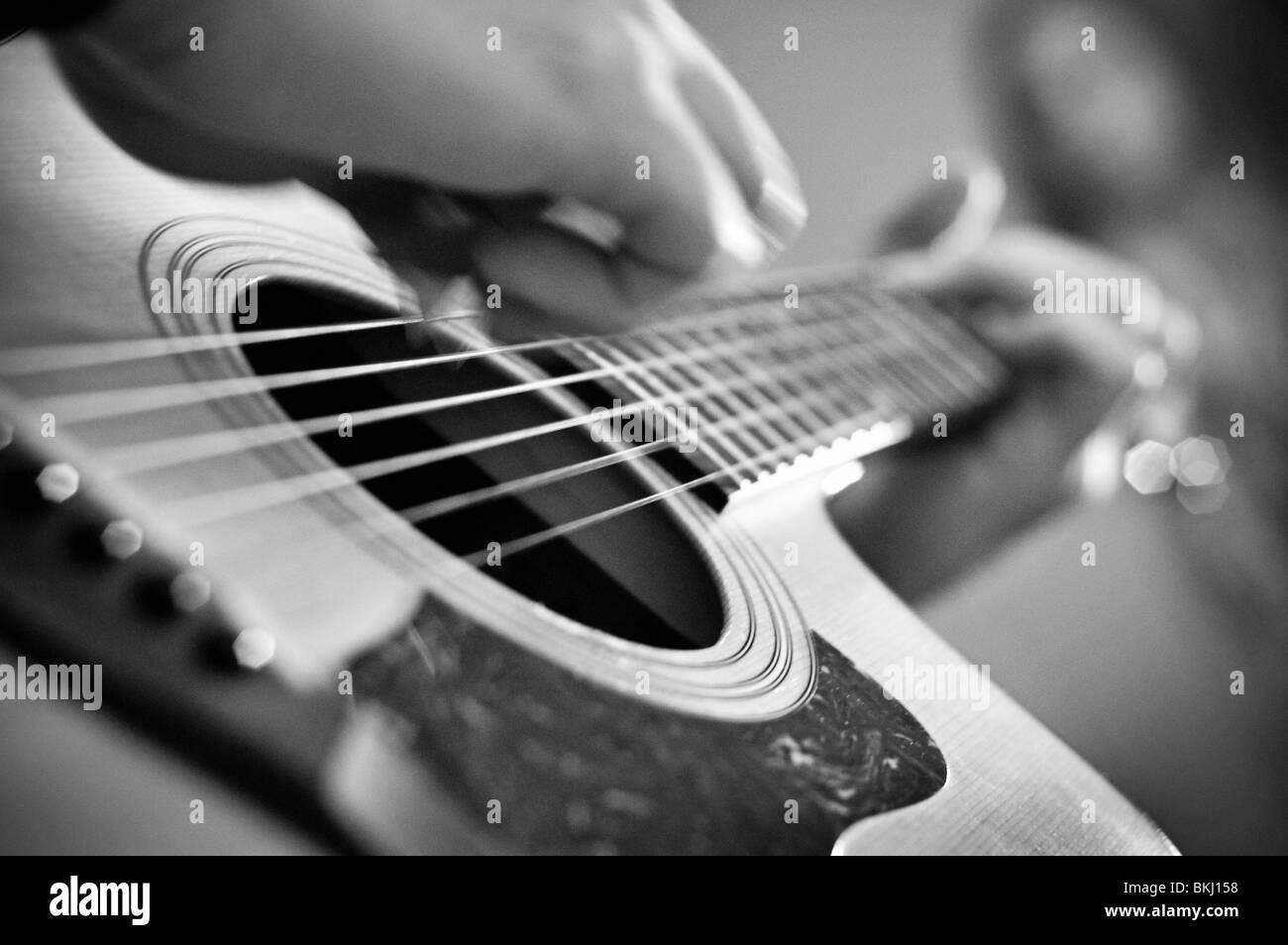Close-up of acoustic guitar plerfoming. - Stock Image