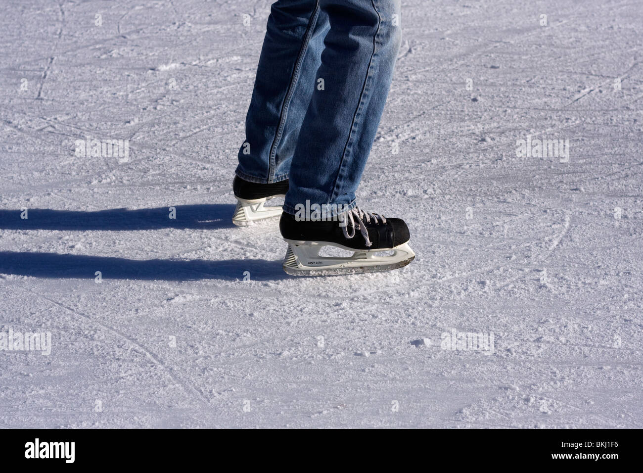 Legs of ice skater on rink. - Stock Image