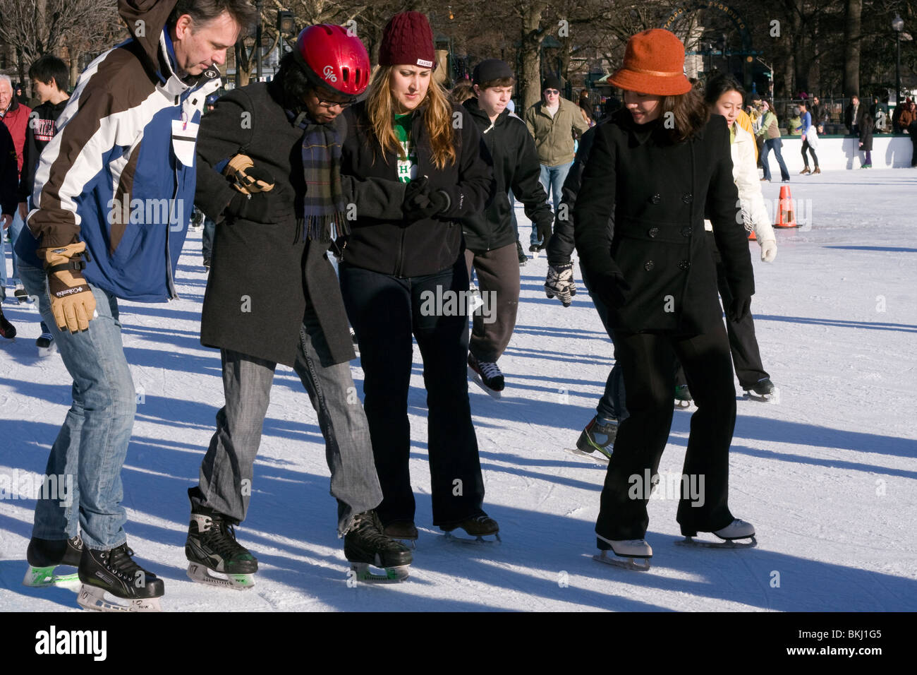 Man being helped by two friends whilst learning how to ice skate. - Stock Image