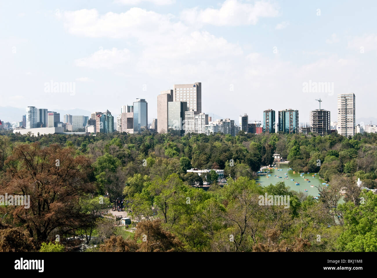 Mexico City skyline seen from Chapultepec Castle looking across Chapultepec Park & people boating on Lago Chapultepec - Stock Image