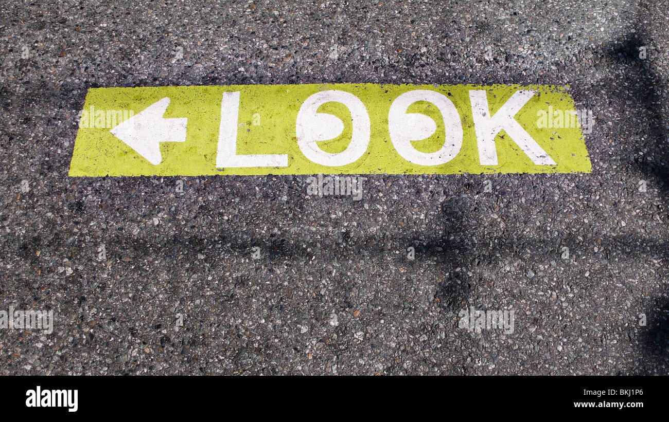 Caution to look both ways street pavement sign. - Stock Image