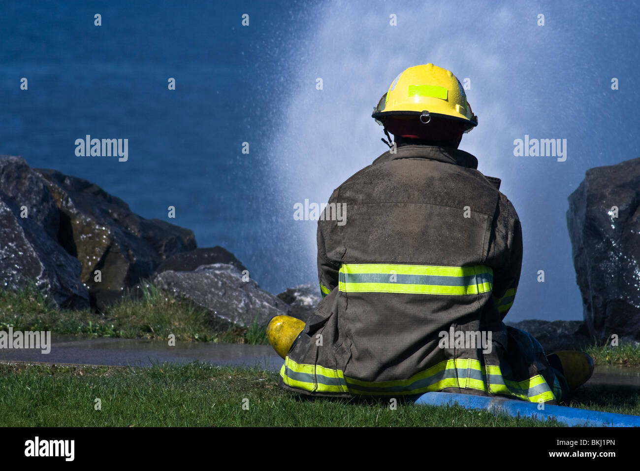 New fireman sitting on a hose under pressure - Stock Image