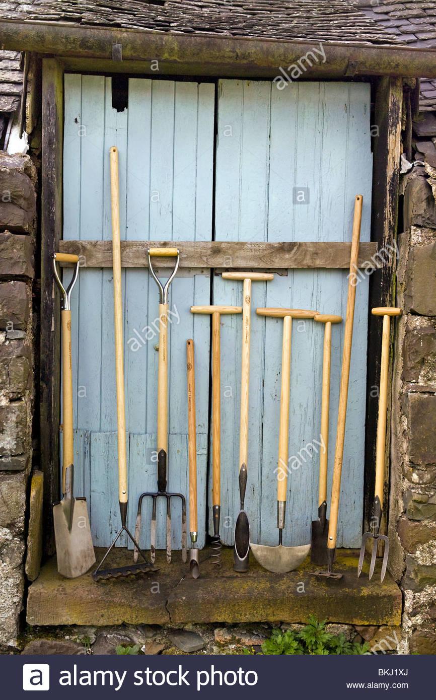 Line up of De Wit garden tools against a blue wooden barn door - Stock Image