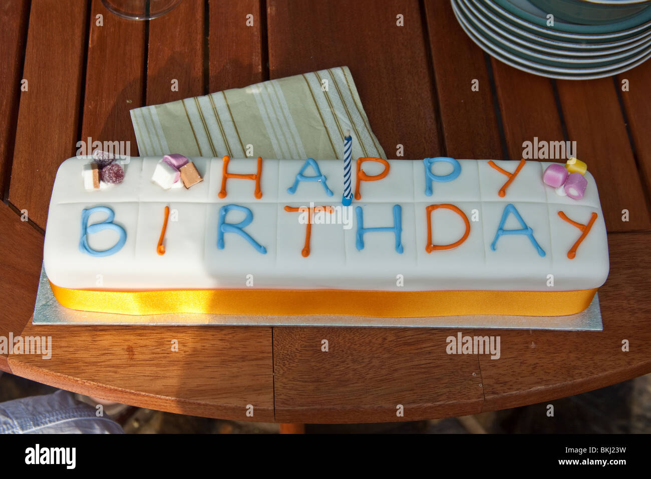 Birthday cake on a wooden table. - Stock Image