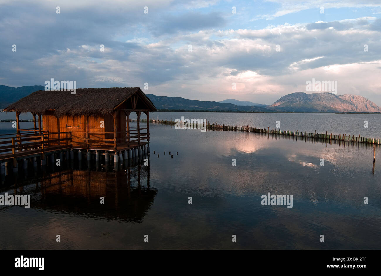 Wooden fisherman house in the middle of  lagoon with calm water of Messolonghi at sunset Stock Photo