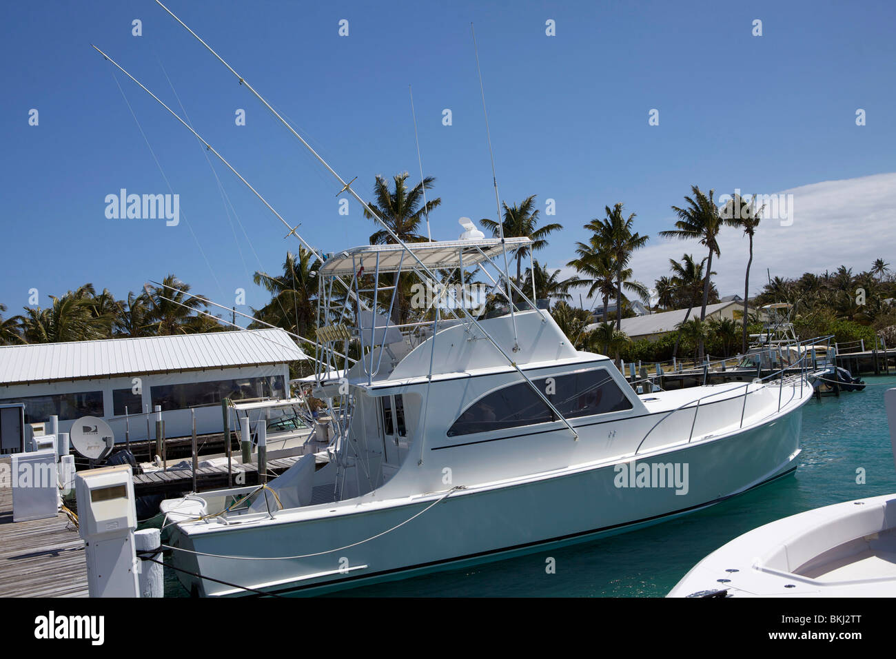 A motor cruiser tied up in a slip at the marina in Man O War Cay. - Stock Image