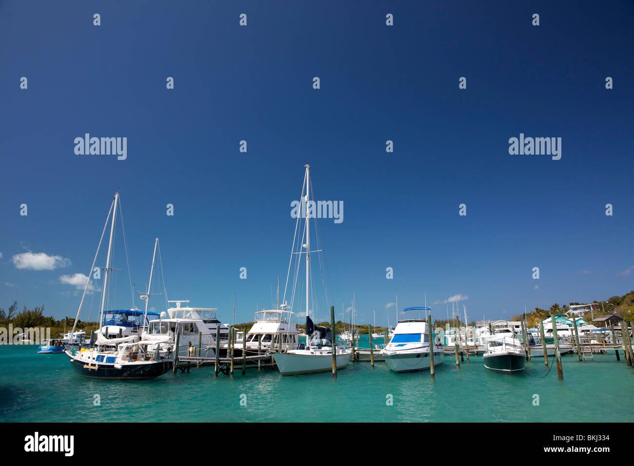 Sailboats and motor boats tied up in slips at the marina in Man O War Cay. - Stock Image