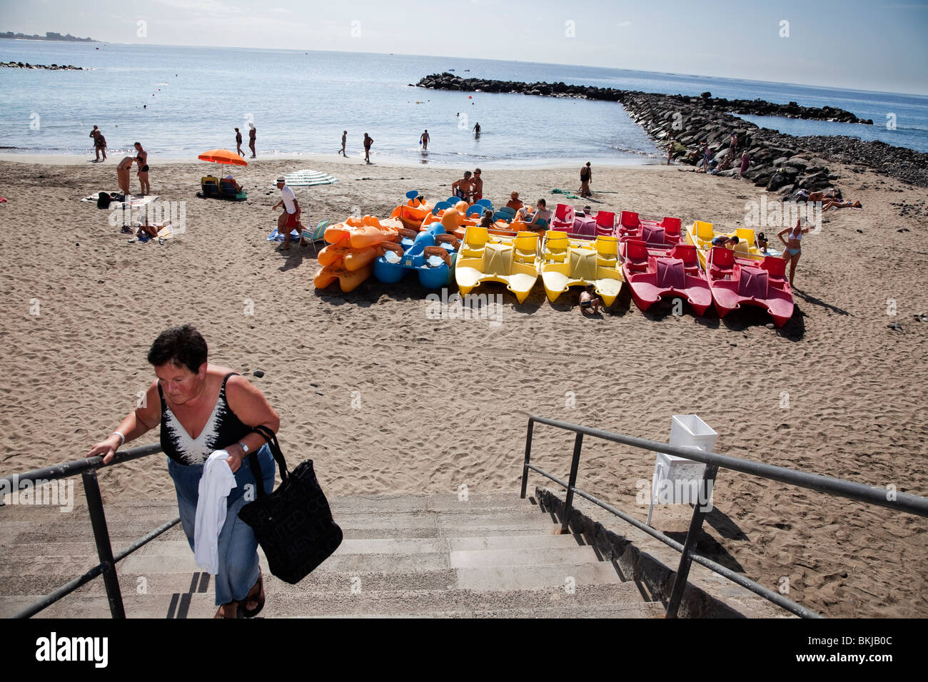 tenerife canary islands costa adeje female middle-aged holidaymaker leaving the beach up stairway - Stock Image