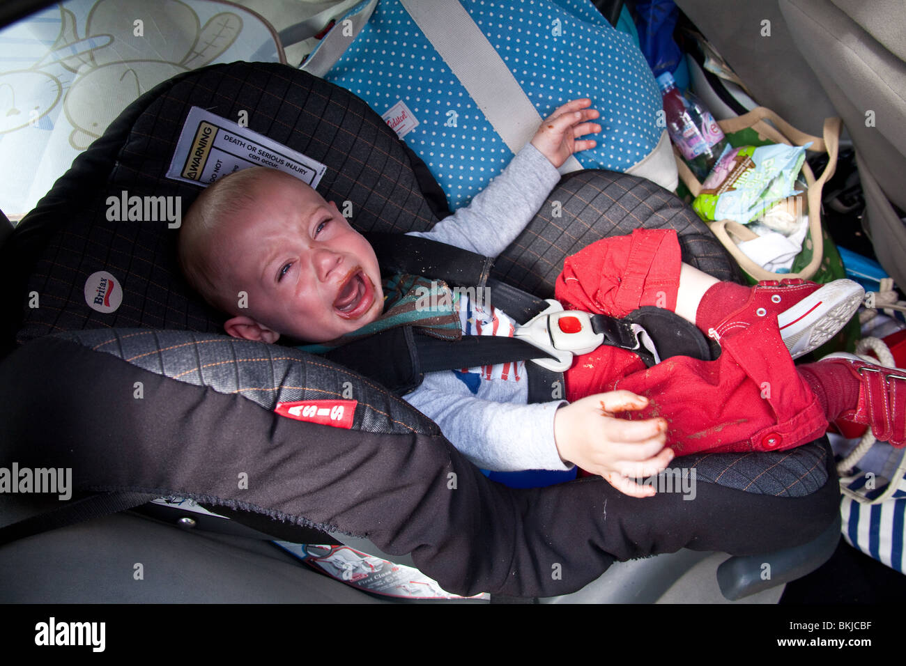 Baby boy (1 year old) in a car seat crying for more chocolate with