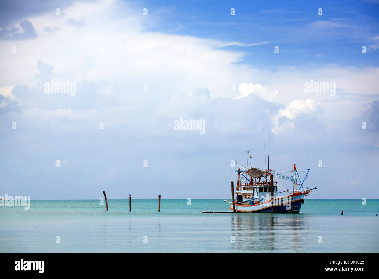 A single fishing boat off the coast of Thailand - Stock Image