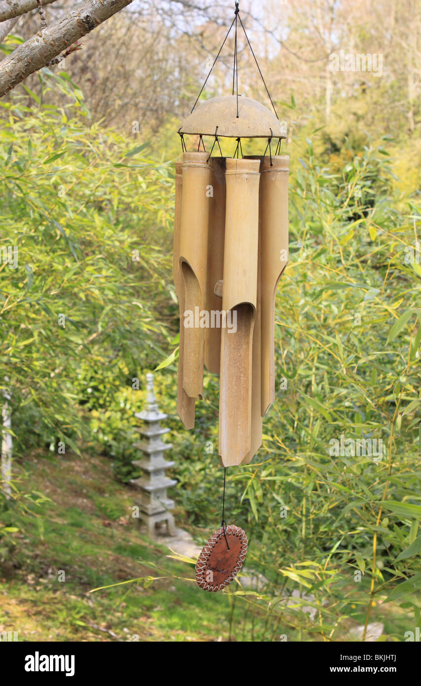 Bamboo wind chime hanging in a garden - Stock Image