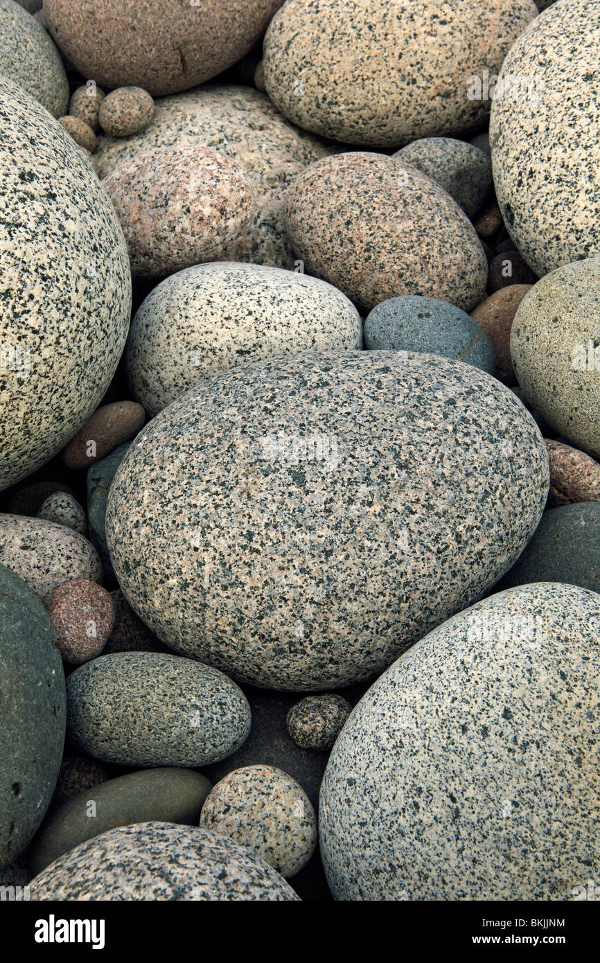 A photograph of smooth round granite rocks on a beach - Stock Image
