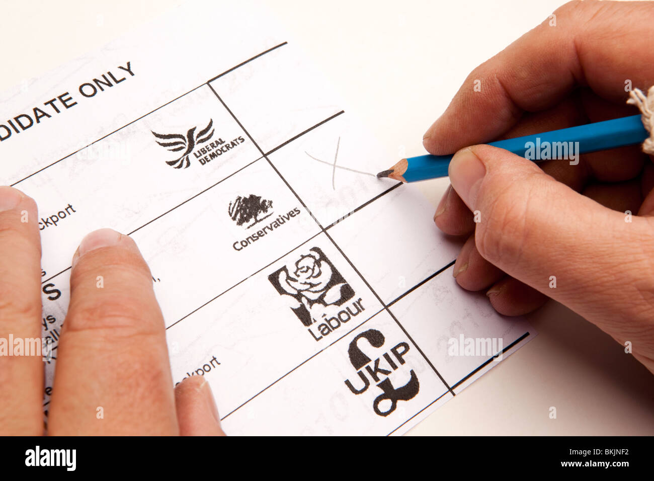 UK Elections man voting on ballot paper for Conservative candidate - Stock Image