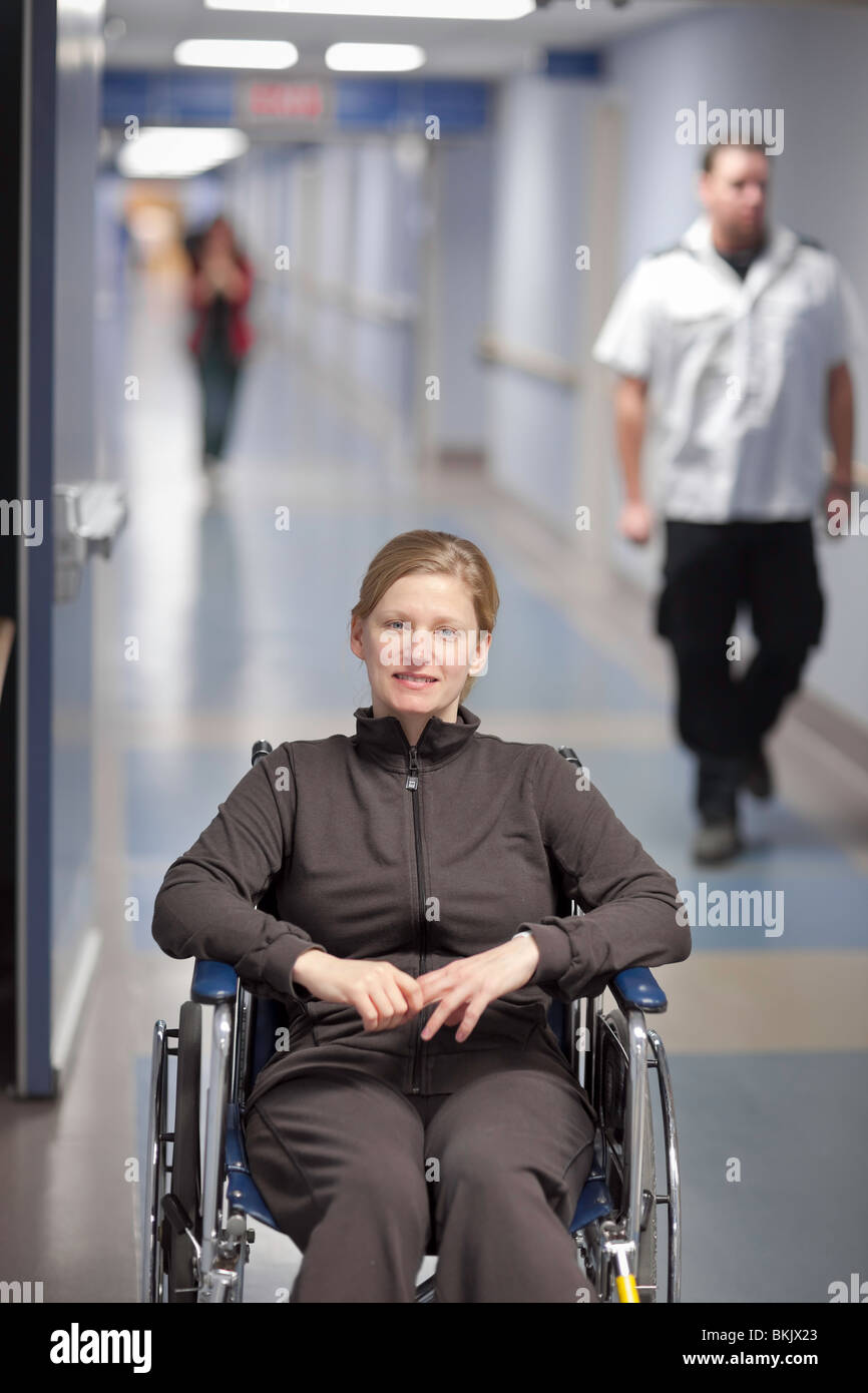 Woman waiting in a wheelchair, in a hospital hallway. - Stock Image