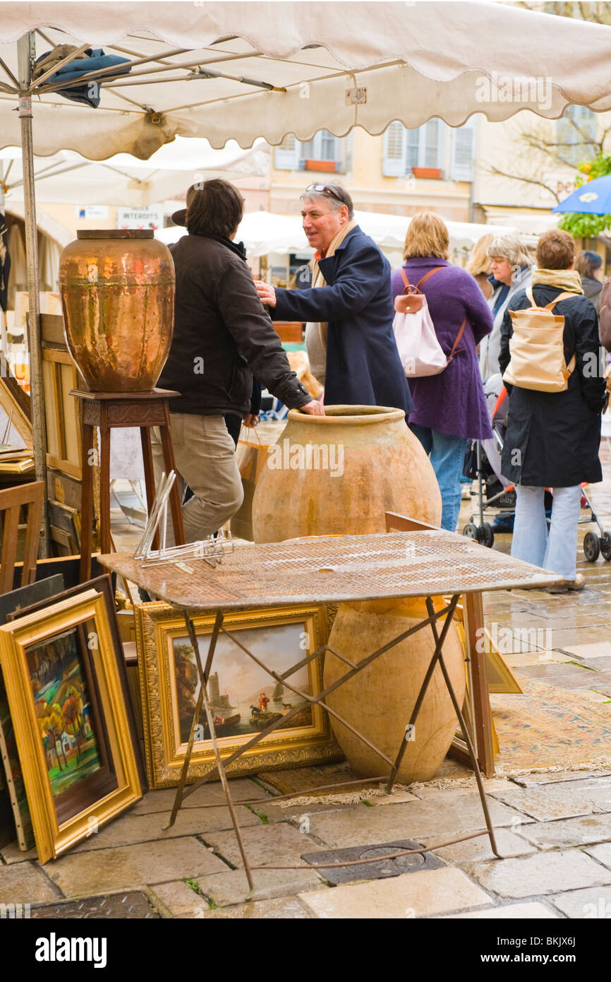 Rainy day in Valbonne , Province , market vendor selling old pictures , paintings & vases or urns - Stock Image