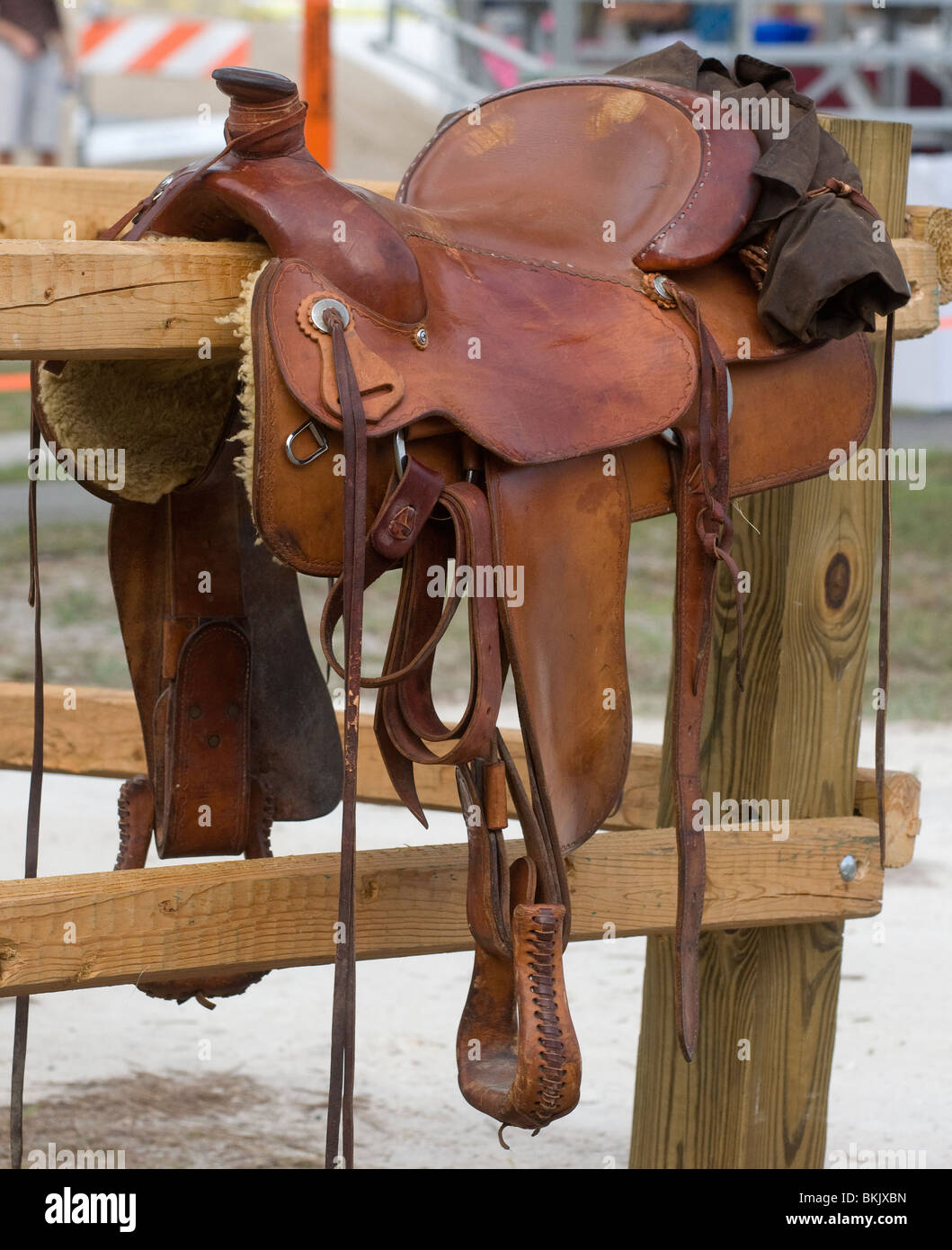 western saddle sits atop wooden fence during Pioneer Days High Springs Florida - Stock Image