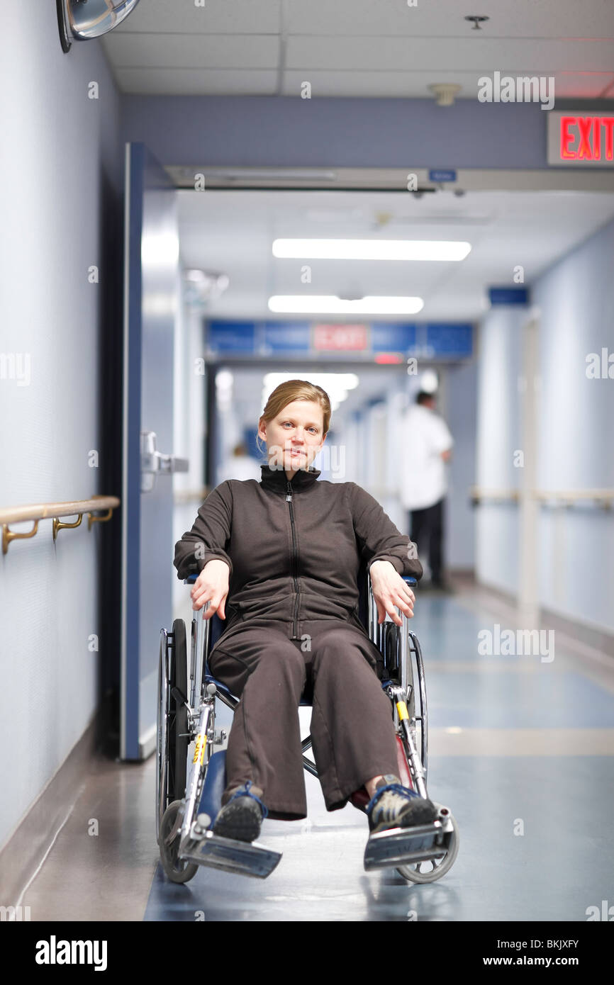 Woman in a wheelchair waiting in a hospital hallway. - Stock Image