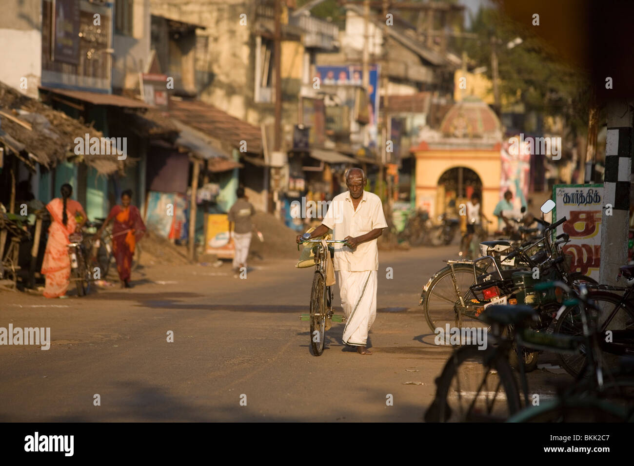 A man pushes his bicycle down a street in the temple town Swamimalai, Tamil Nadu, India - Stock Image