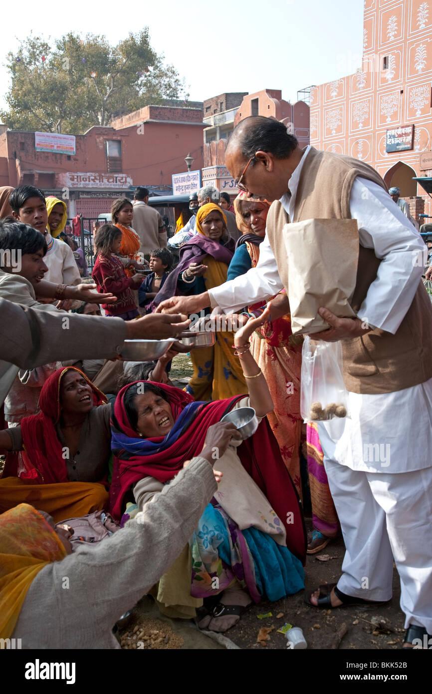 Man giving food to beggars. Jaipur. Rajasthan. India - Stock Image