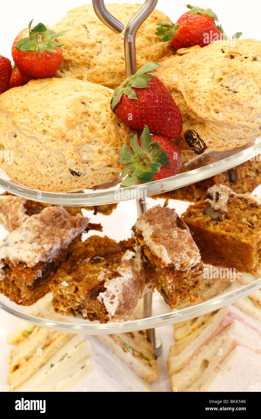 cake stand with Strawberries and scones, Walnut cake sponge, ham and egg sandwiches desert Wedding breakfast table - Stock Image