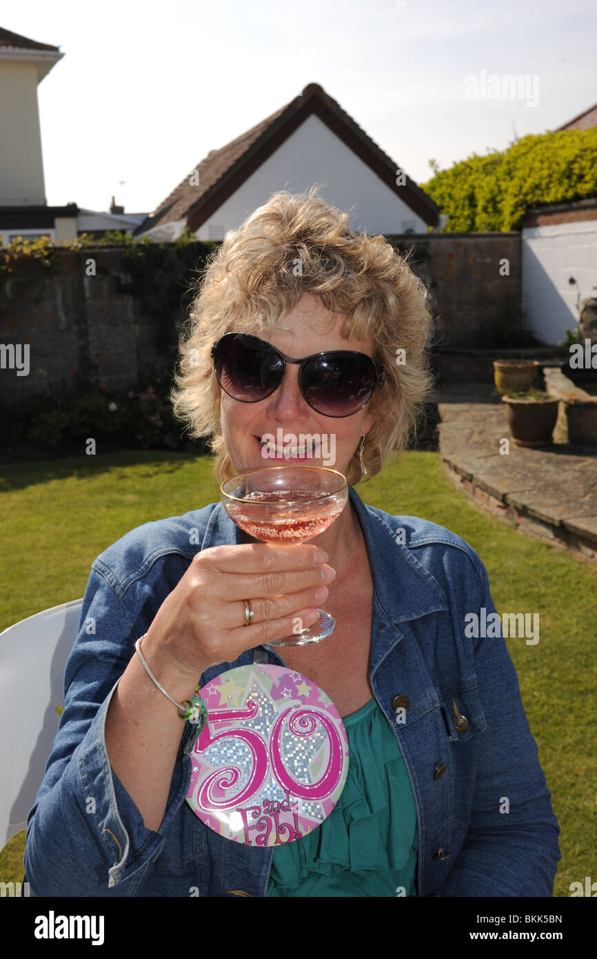 Blonde woman celebrating her 50th birthday glass of champagne pink - Stock Image
