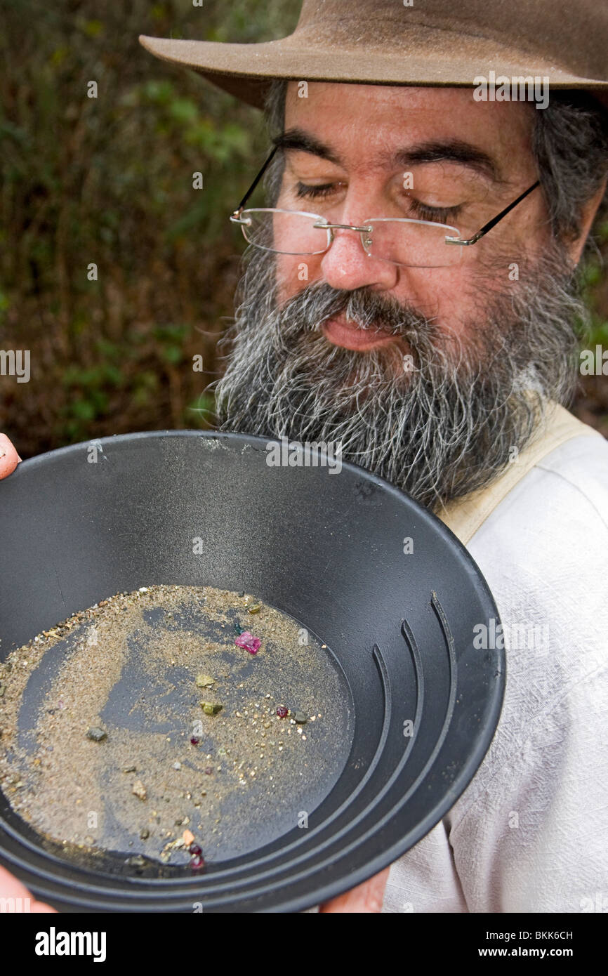 Man looks closely at gold mine pan with gems during