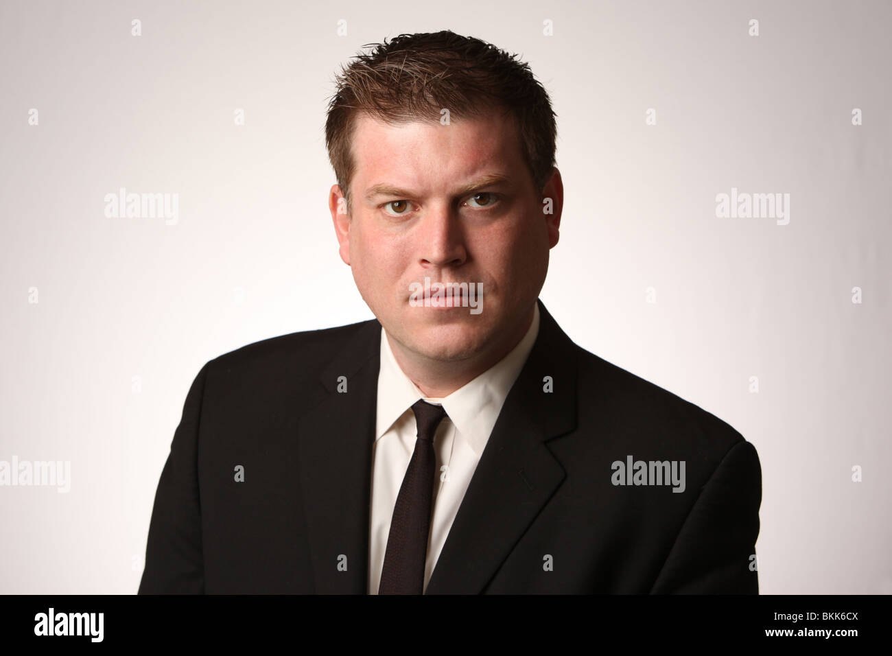 Serious business man wearing black suit and tie.  © Katharine Andriotis - Stock Image