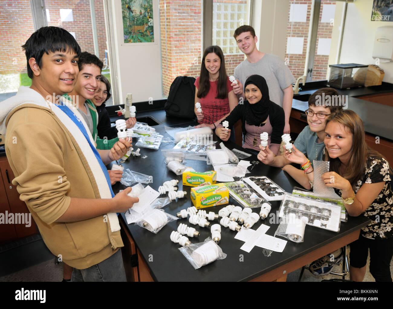 High school environmental club meeting. Students are preparing energy efficient lightbulbs to give away to the community. - Stock Image