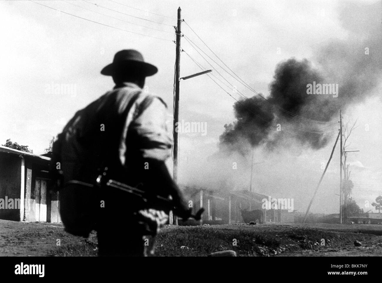 A shell lands nearby (from a Hutu gun placement) as the RPF troops advance to Kigali during the Rwandan genocide - Stock Image