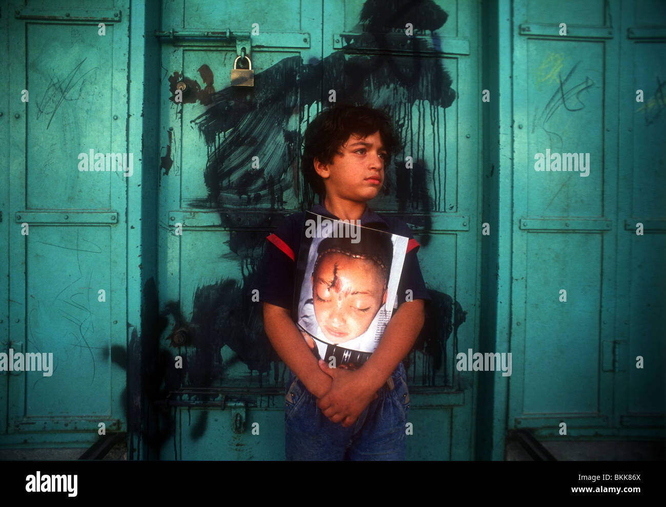 A portrait of Palestinian boy in the Gaza Strip holding a photograph of his sister killed in the intifada war. - Stock Image