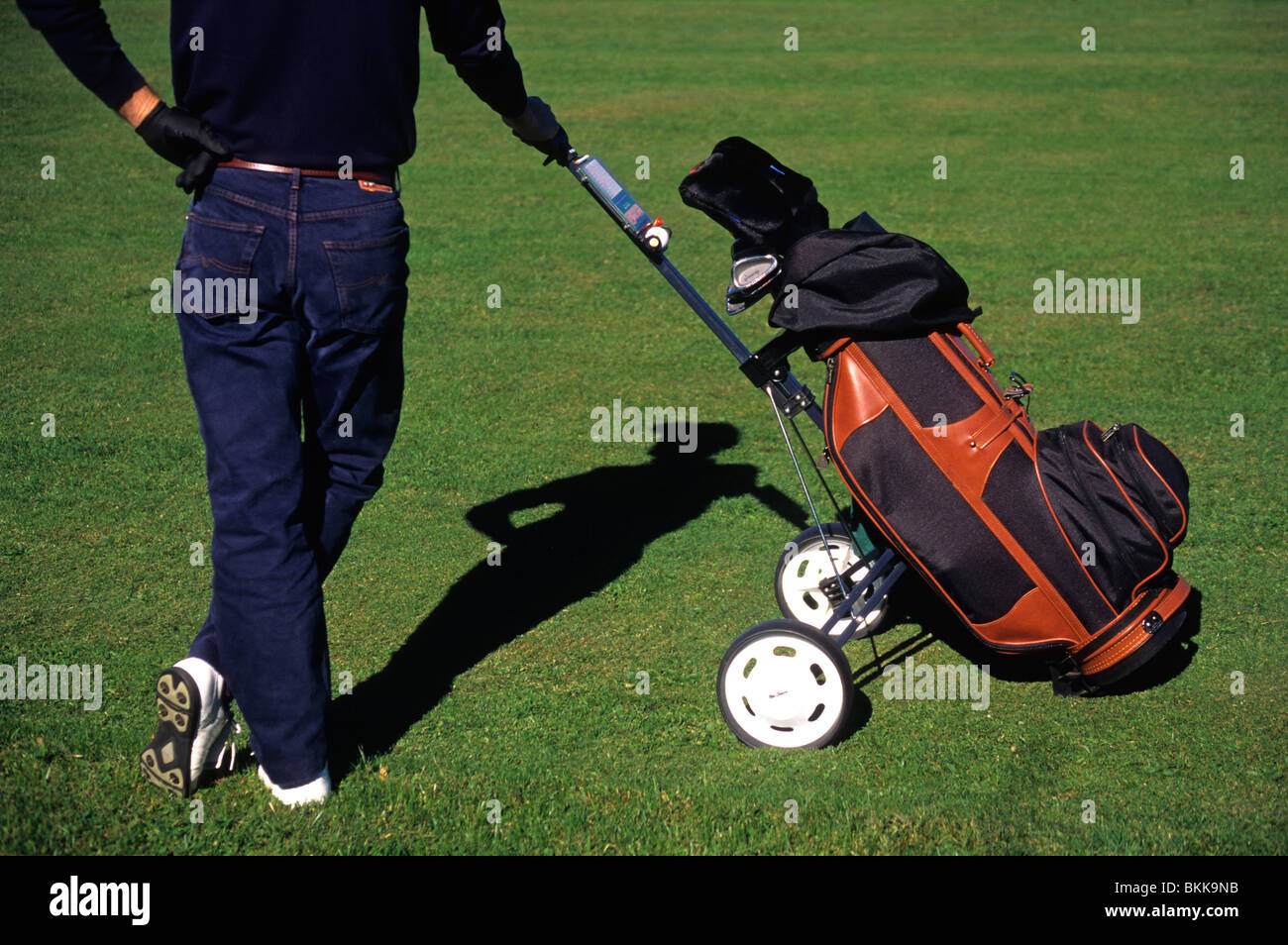 Golfer / Caddy holding his golf bag / trolley - Stock Image