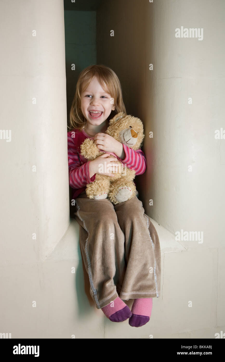 Three Year Old Girl Sitting in Stove Recess - Stock Image