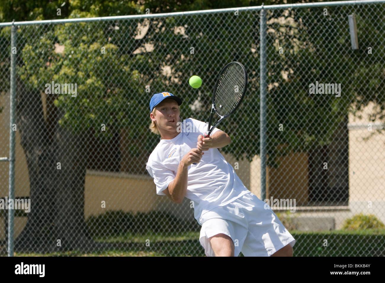 Men's tennis player hitting tennis ball - Stock Image