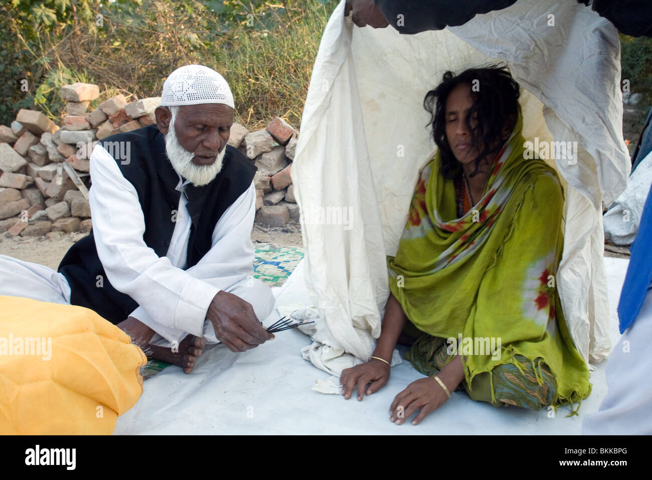 A Sufi holy man or Pir, exorcises a spirit from a woman at a dargah or shrine in South Delhi, India - Stock Image