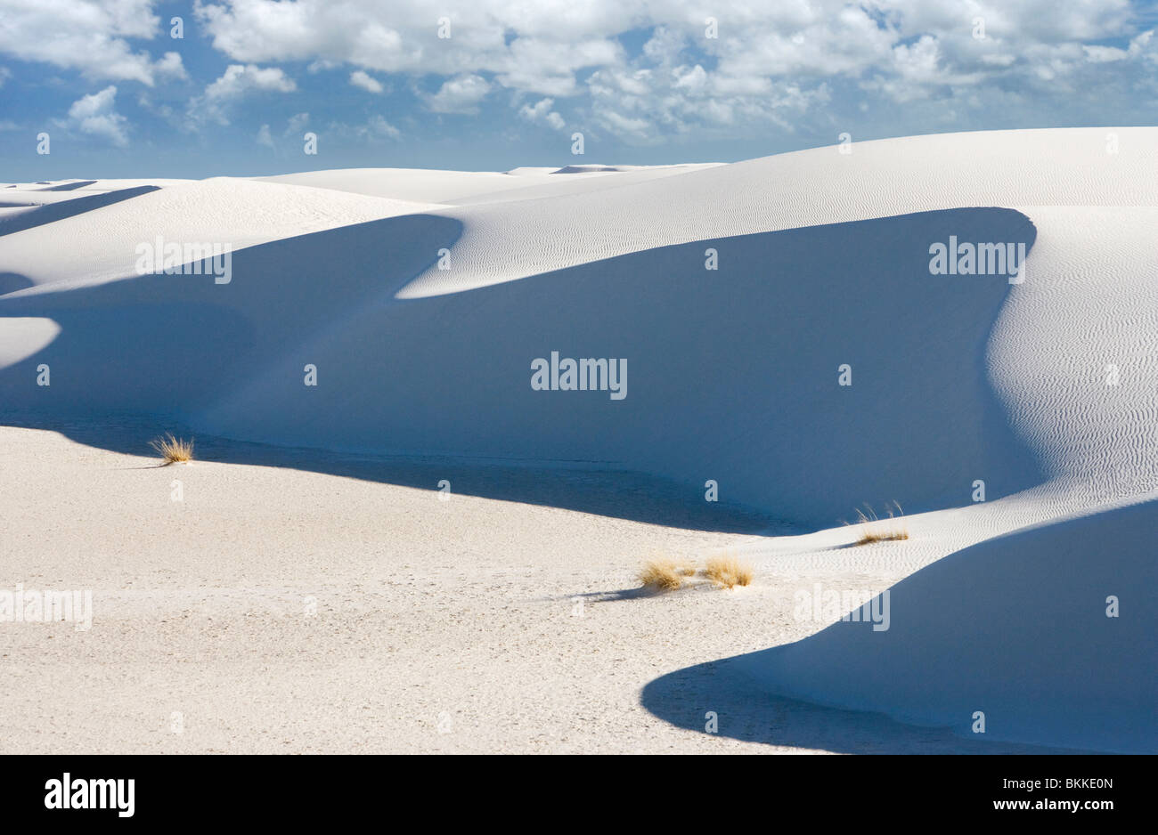 A person walking up a large white sand dune at White Sands National Monument, New Mexico. - Stock Image