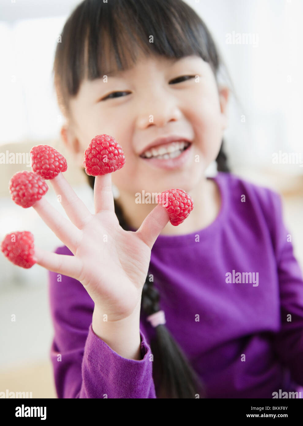 Chinese girl with raspberries on fingers Stock Photo