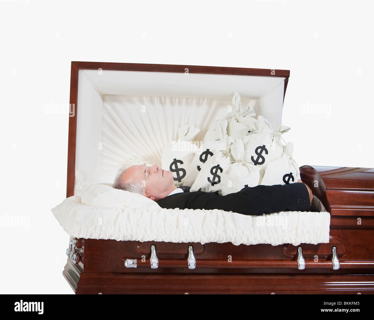 A Deceased Man In A Coffin Surrounded By Bags Of Money - Stock Image