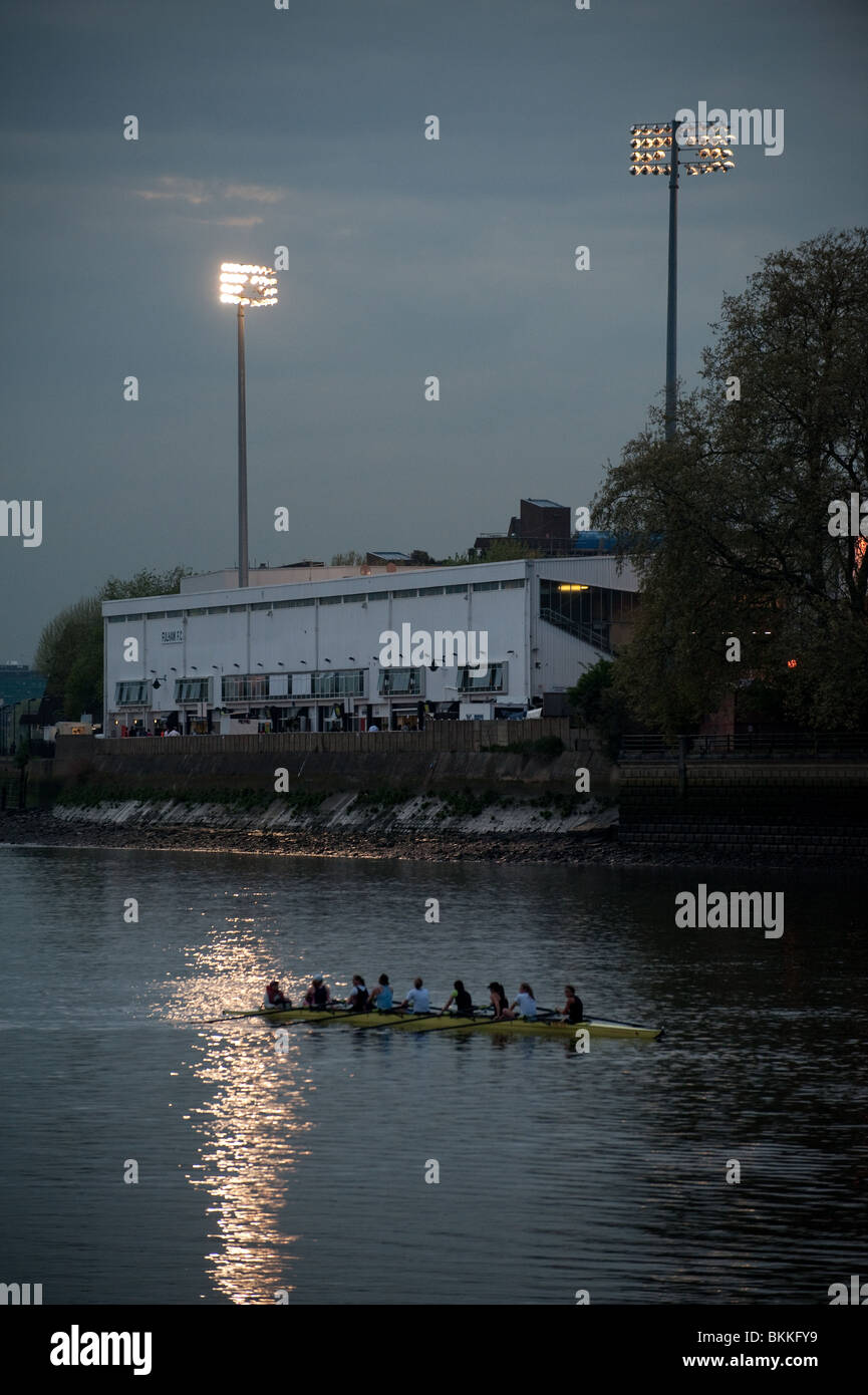 A boat full of rowers glides past Craven Cottage football ground at dusk as the floodlights glimmer on London's - Stock Image