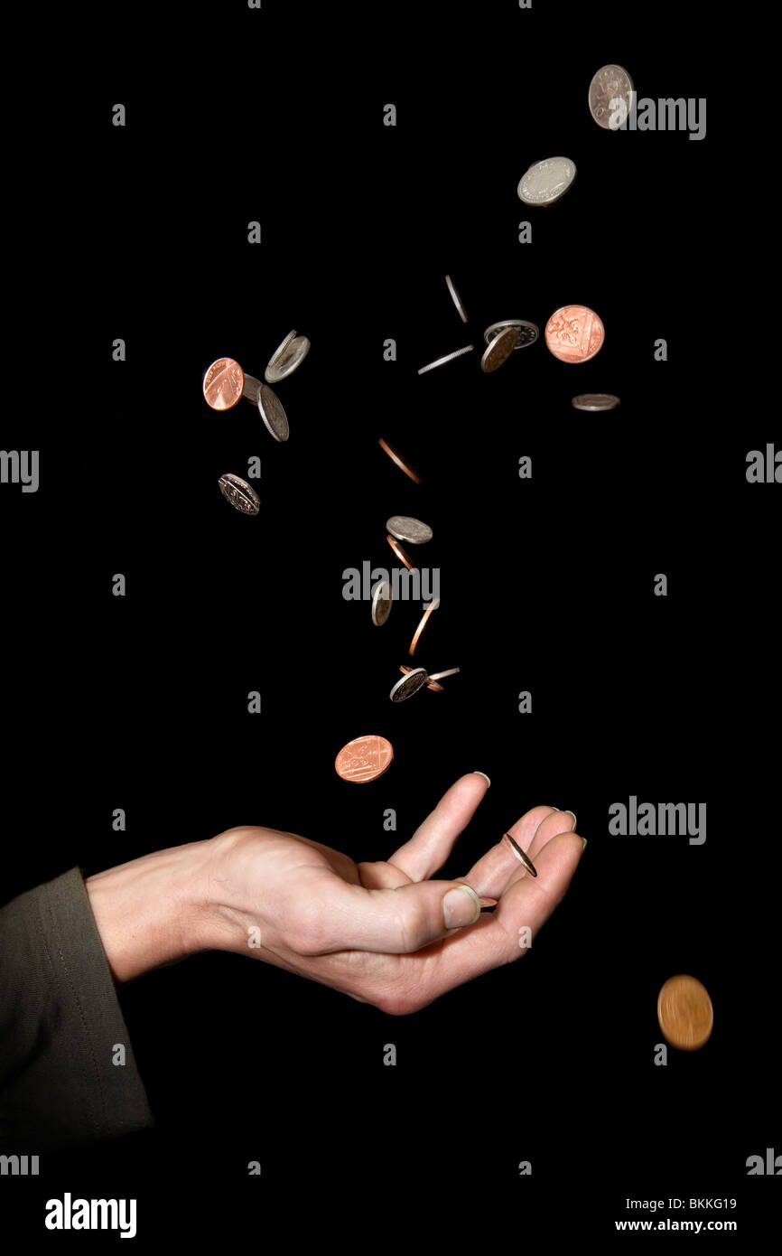 42 yr old Caucasian male hand held out depicting concept its raining money, money falling from the sky or pennies - Stock Image