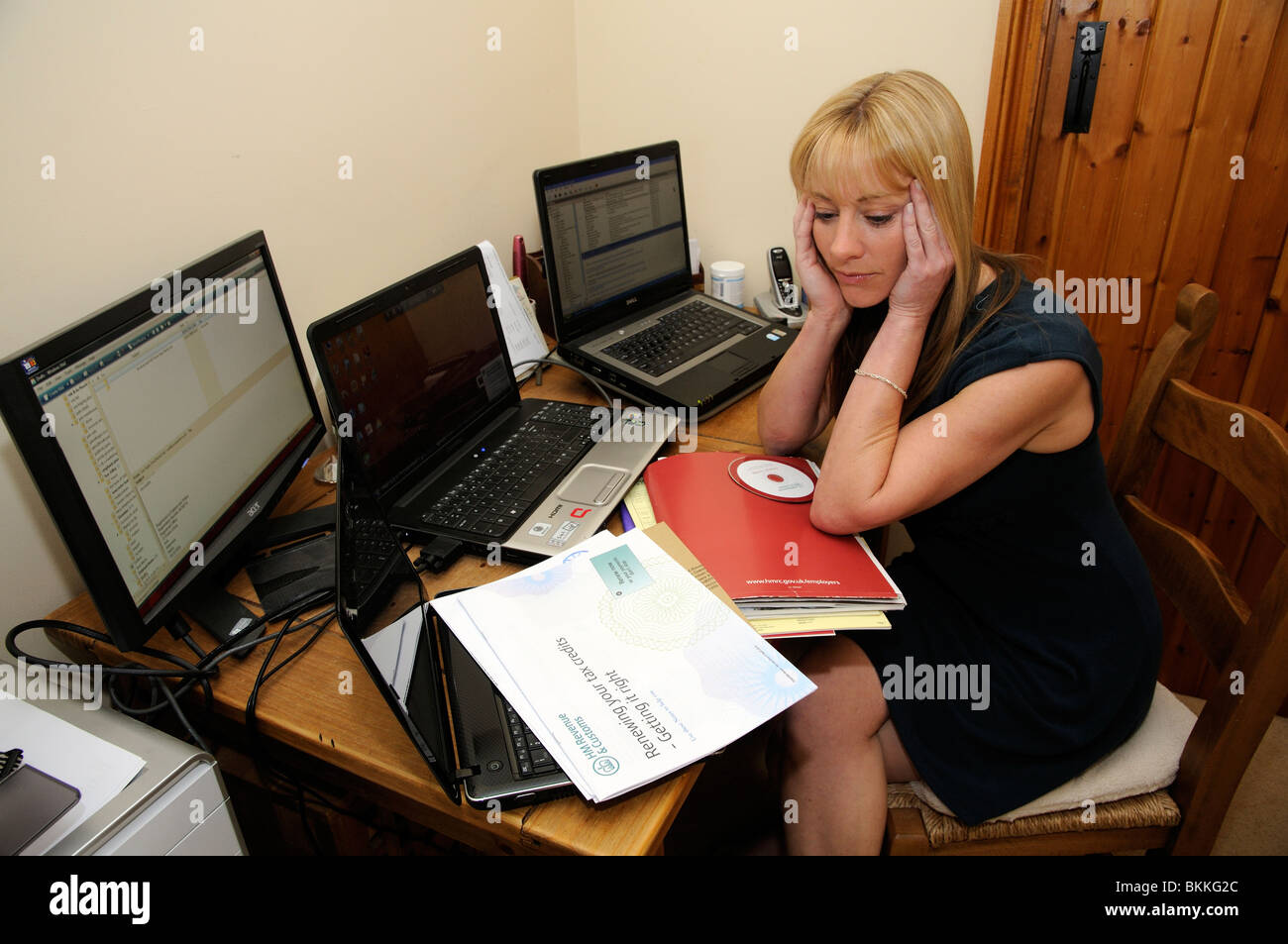 Working from home a woman working on annual accounts from a small office within her house Stock Photo
