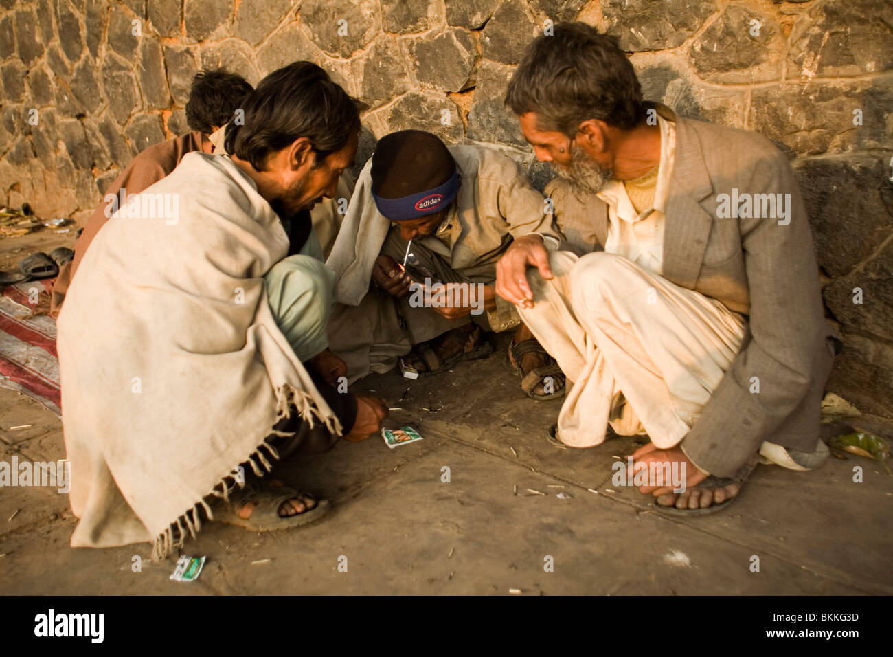 A group of homeless men smoke cheap heroin in an area full of the destitute and poor near the Jama Masjid. Delhi, - Stock Image