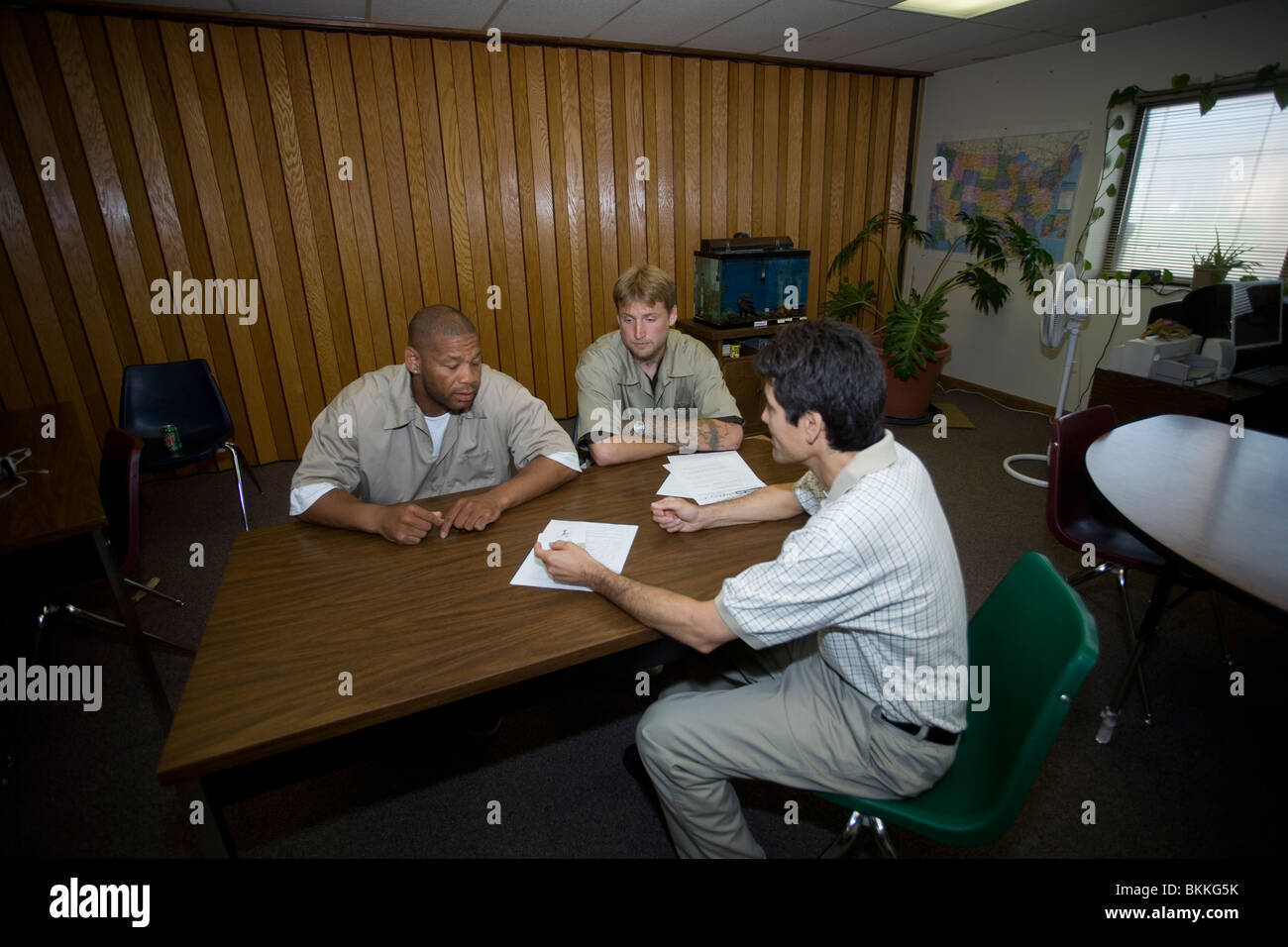Two inmates talking with teacher. Many inmates desperately need education to have a chance to stay out after release. - Stock Image