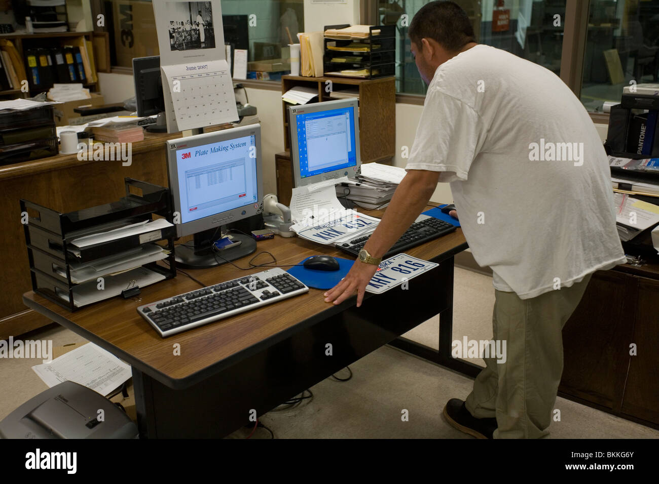Inmate working at license plate manufacturing computer and printer at the Nebraska State Penitentiary, Lincoln, - Stock Image