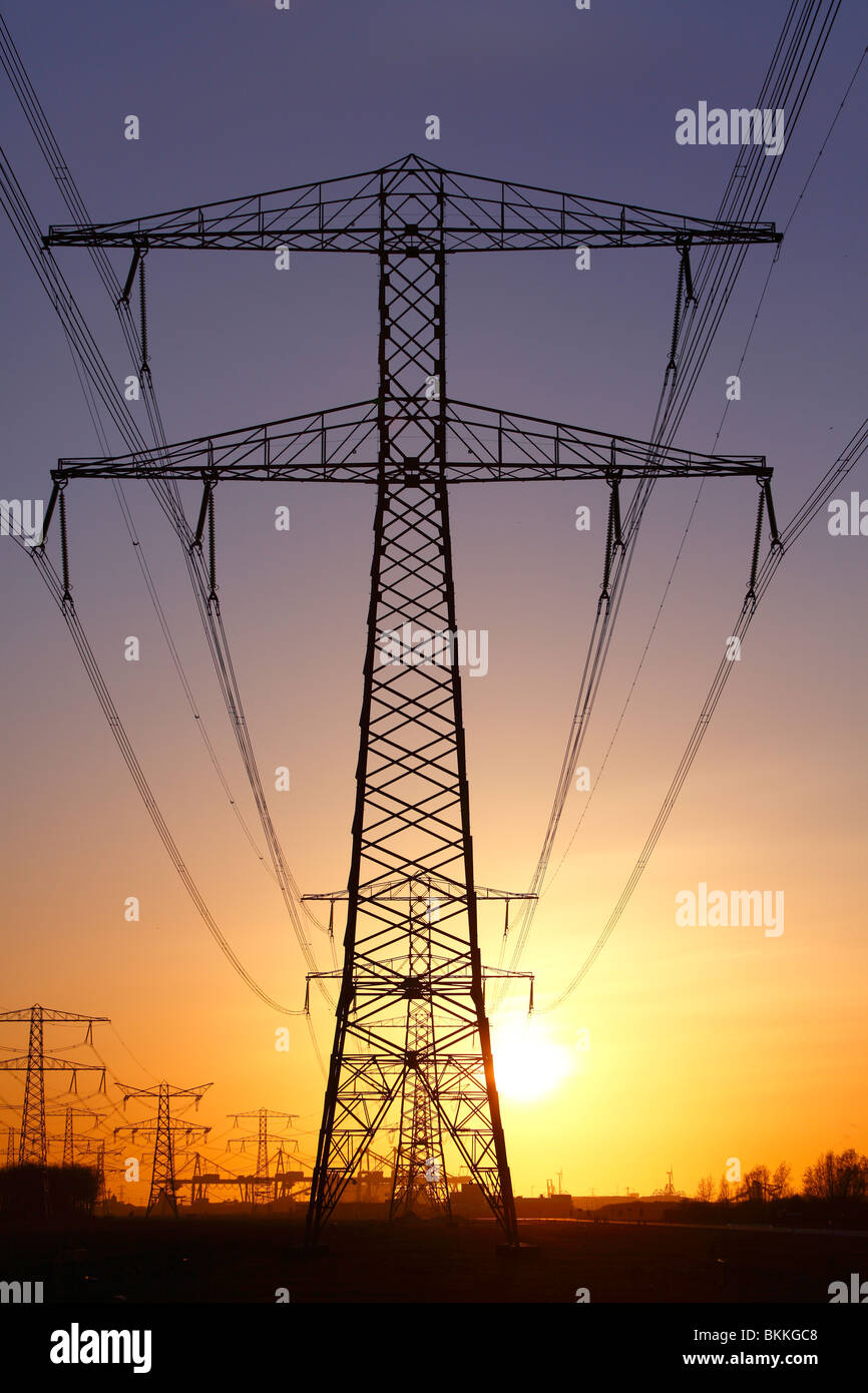 Powerlines and towers during orange sunset due to volcanic ash from  2010 Iceland Eyjafjallajökull volcano - Stock Image