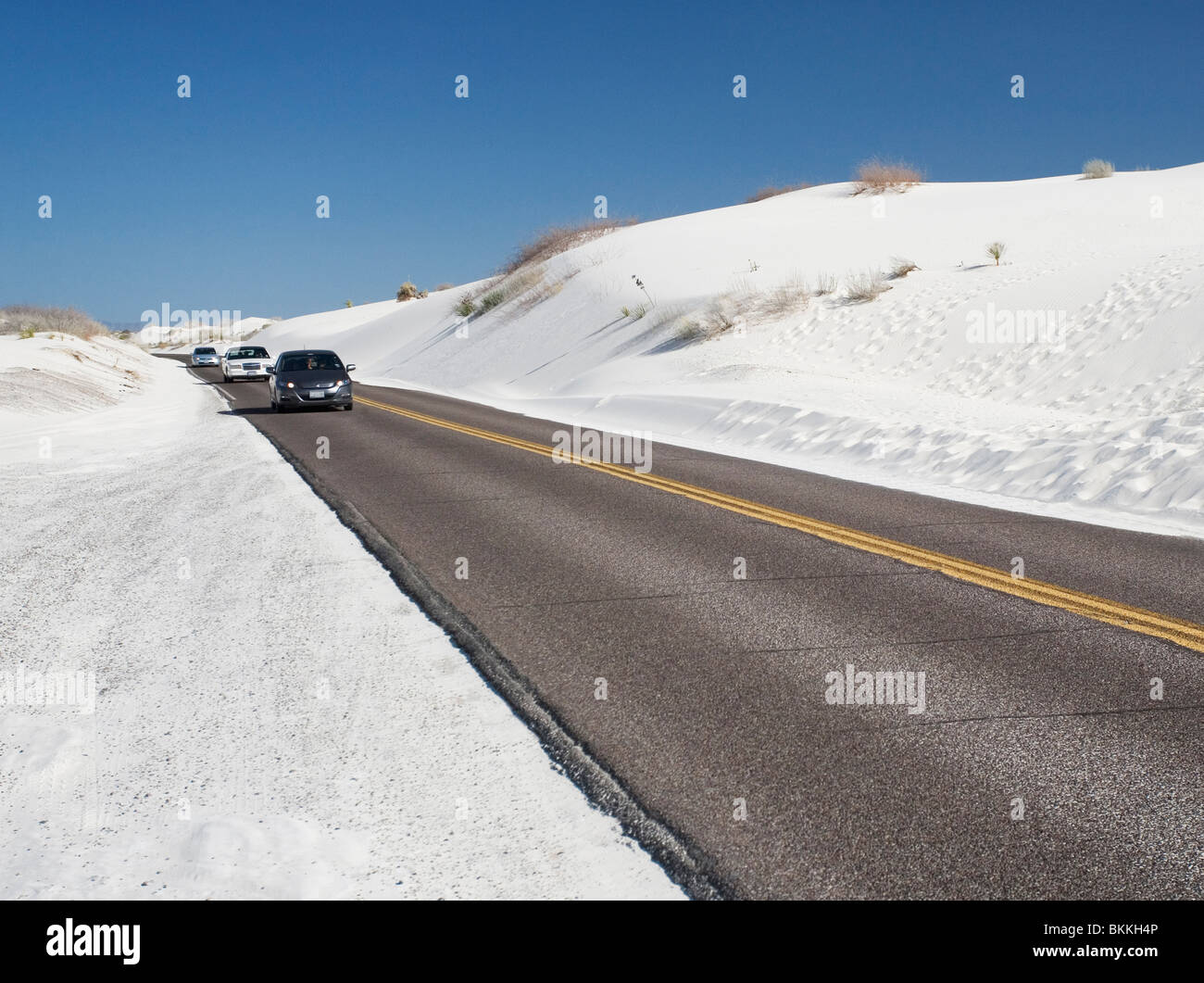 Cars drive on the loop road through White Sands National Monument, New Mexico. - Stock Image