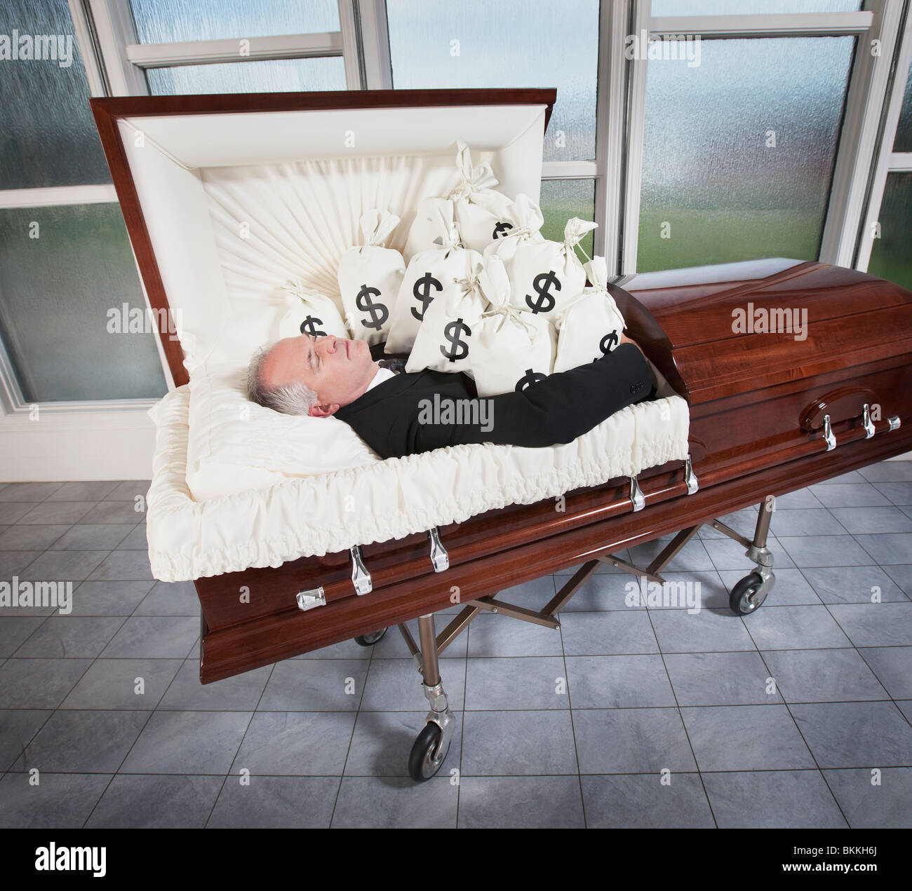 A Man Laying In A Coffin Surrounded By Bags Of Money - Stock Image