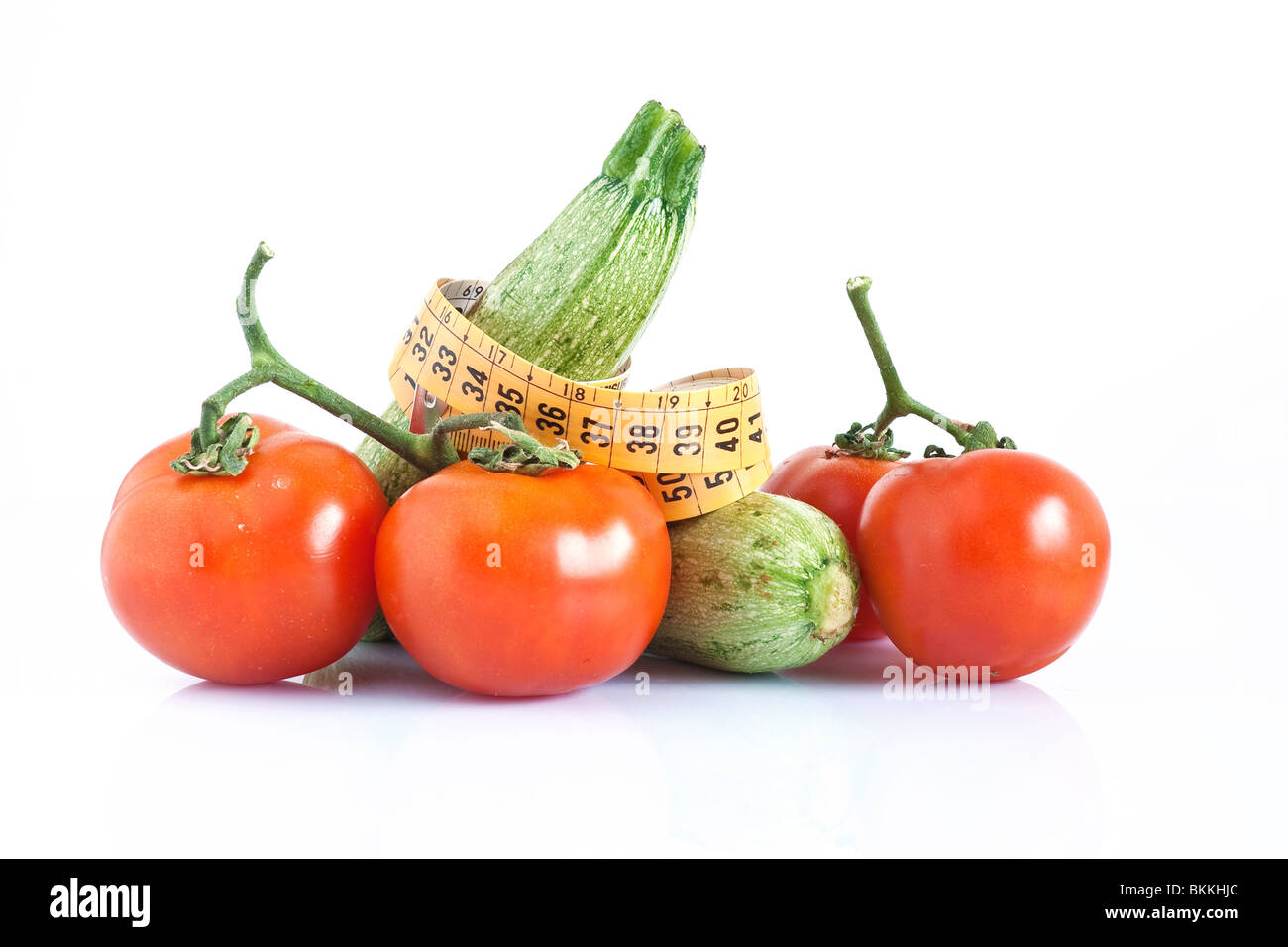 two courgettes and tomatoes with meter isolated on white background - Stock Image