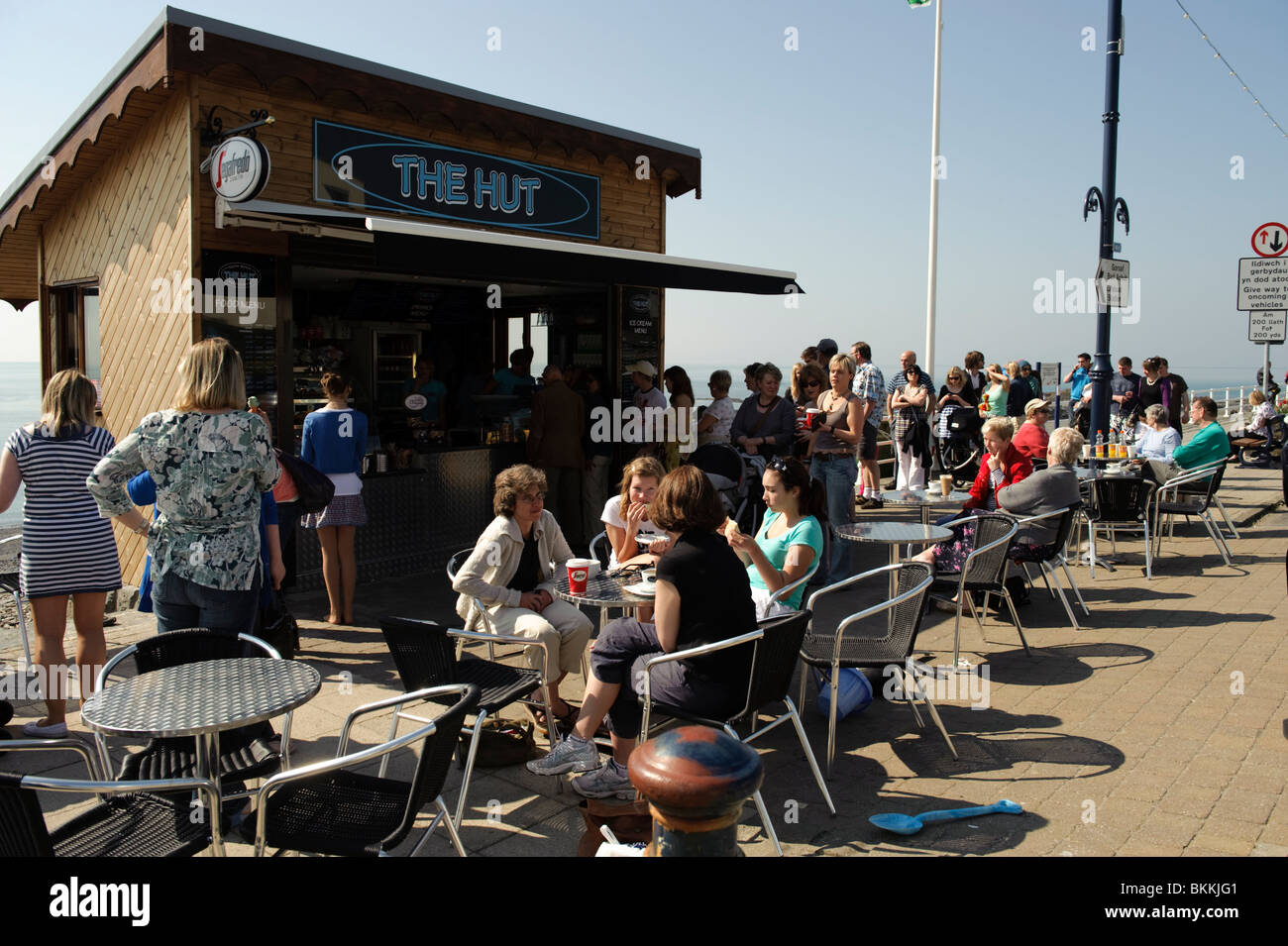 Crowds of people outside The Hut, seaside icecream parlour cabin cafe, Aberystwyth south promenade, Wales UK - Stock Image